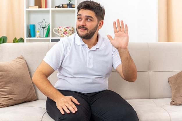 Молодой человек в повседневной одежде смотрит в сторону с улыбкой на лице и машет рукой, сидя на диване в светлой гостиной