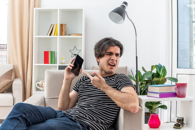 가벼운 거실의 의자에 앉아 휴대 전화로 이야기하는 동안 혼란스럽고 불쾌한 캐주얼 옷을 입은 젊은 남자