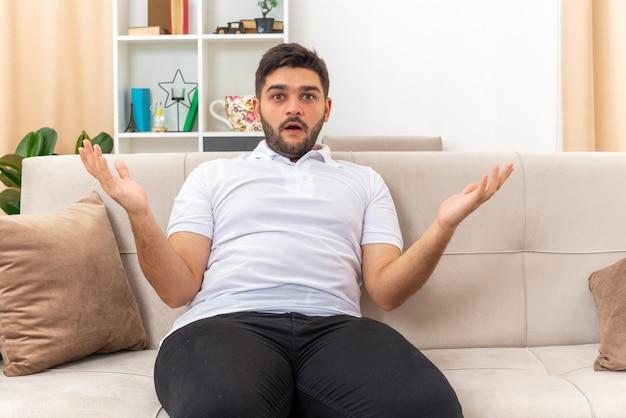 Молодой человек в повседневной одежде выглядит смущенным и удивленным, раскинув руки в стороны, сидя на диване в светлой гостиной