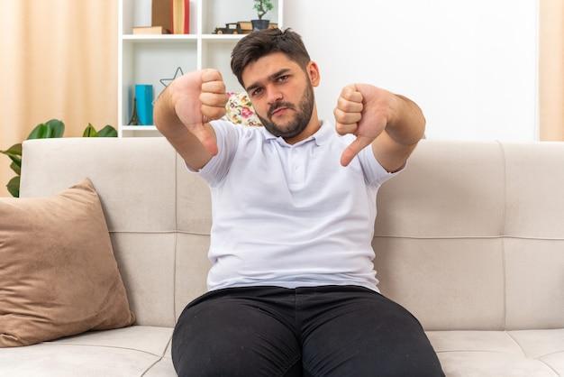 가벼운 거실에서 소파에 앉아 아래로 엄지 손가락을 보여주는 불쾌감을 보이는 캐주얼 옷을 입은 젊은 남자