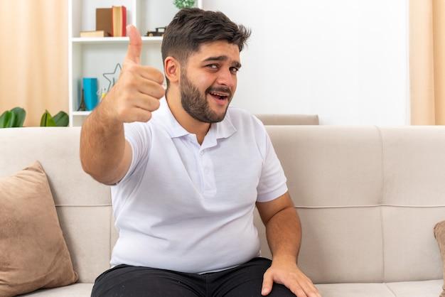 明るいリビング ルームのソファに座って親指を出て幸せで陽気なカジュアルな服を着た若い男