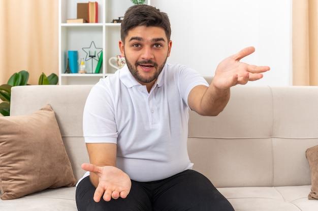 Молодой человек в повседневной одежде выглядит счастливым и взволнованным, сидя на диване в светлой гостиной