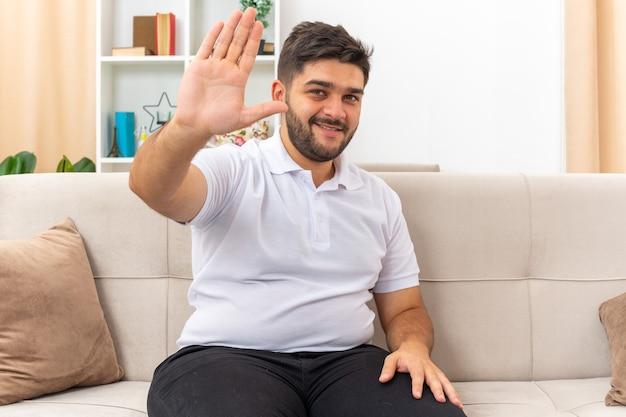 밝은 거실에서 소파에 앉아 행복하고 긍정적 인 손으로 행복하고 긍정적 인 손을 흔들며 찾고 캐주얼 옷을 입은 젊은 남자