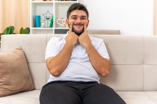 明るいリビング ルームのソファに座っている彼の偽の笑顔を人差し指で指しているカジュアルな服を着た若い男