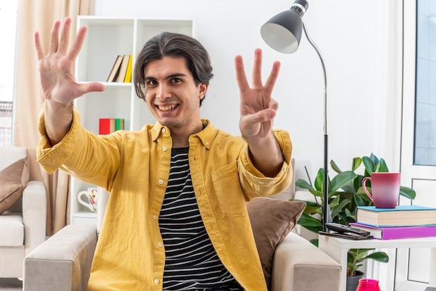캐주얼 옷을 입은 젊은 남자가 밝은 거실의 의자에 앉아있는 여덟 번째를 유쾌하게 보여주는 미소를 찾고 있습니다.