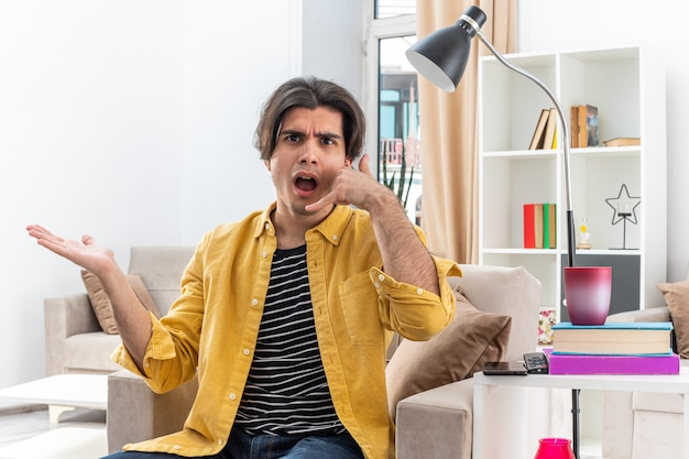 놀랍고 혼란스러운 캐주얼 옷을 입은 젊은 남자가 가벼운 거실의 의자에 앉아 제스쳐를 불러주세요.