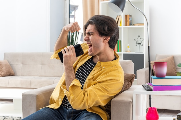 가벼운 거실에서 의자에 앉아 주먹을 떨림 휴대 전화로 이야기하는 동안 화가 외치는 캐주얼 옷에 젊은 남자