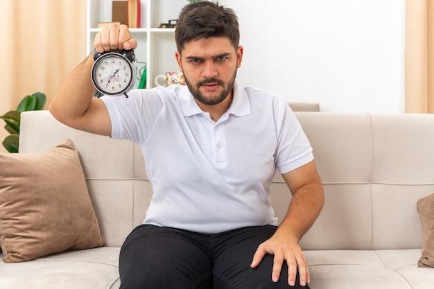 Молодой человек в повседневной одежде показывает будильник и смотрит с серьезным хмурым лицом, сидя на диване в светлой гостиной