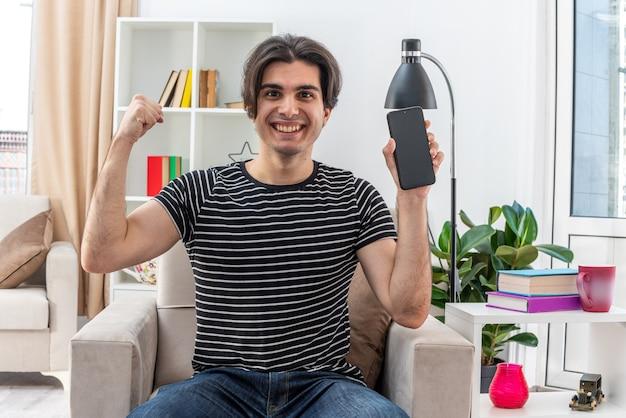 Молодой человек в повседневной одежде показывает смартфон, поднимающий кулак, как победитель, счастливый и позитивный, сидя на стуле в светлой гостиной