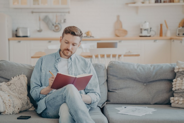 Молодой человек в повседневной одежде сидит на диване со скрещенными ногами, записывает информацию в красный блокнот, делает важные заметки карандашом, организует и планирует свой день