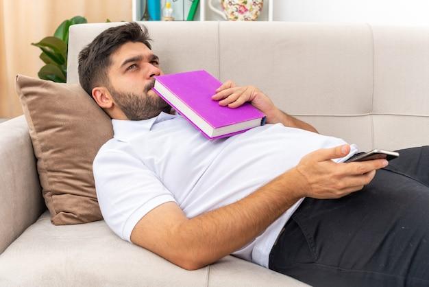 Молодой человек в повседневной одежде с книгой смотрит озадаченно, проводя выходные дома, лежа на диване в светлой гостиной