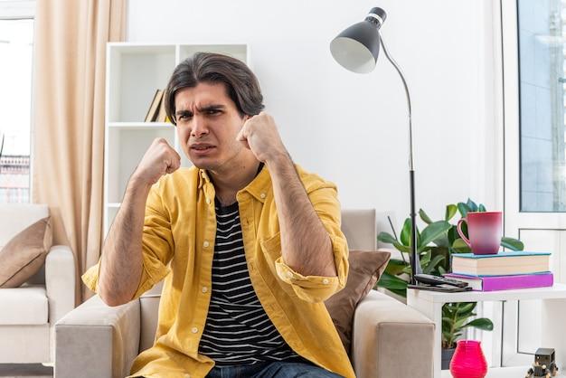 떨리는 주먹으로 캐주얼 옷을 입은 젊은 남자가 진지하고 자신감이 밝은 거실의 의자에 앉아있다.