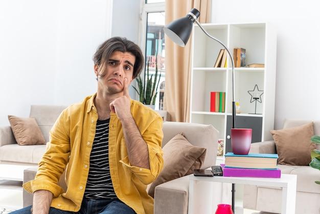 明るいリビング ルームの椅子に座って、悲しそうな表情のカジュアルな服を着た若い男が目の隅を引き下げる