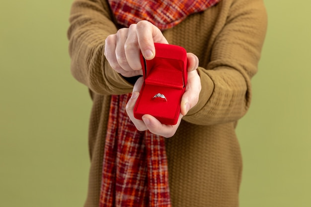 녹색 벽 위에 약혼 반지 발렌타인 데이 개념 서 빨간색 상자를 보여주는 목 스카프와 캐주얼 옷에 젊은 남자