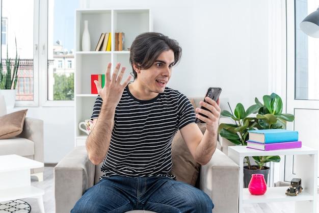 Молодой человек в повседневной одежде со смартфоном выглядит изумленным и удивленным, сидя на стуле в светлой гостиной