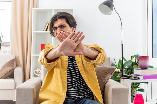 明るいリビング ルームの椅子に座って腕を組んで手を止めるジェスチャーをするカジュアルな服を着た若い男を心配している