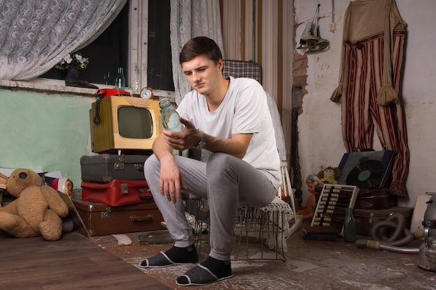 정크 룸에서 병을 들고 있는 동안 케이지에 앉아 캐주얼 의류에 젊은 남자.