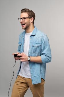 Молодой человек в повседневной джинсовой рубашке держит джойстик или геймпад, играя в игру