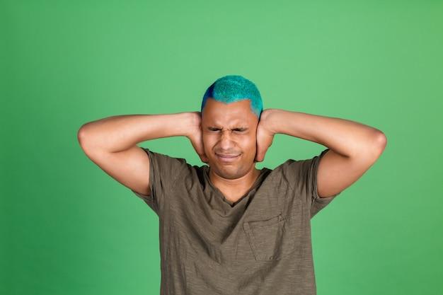 緑の壁にカジュアルな若い男が手で耳を覆う