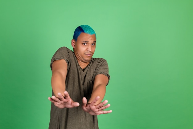 Молодой человек в повседневной одежде на зеленой стене, покрытый руками в страхе от отвращения