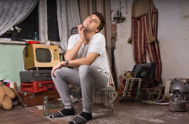 Молодой человек в повседневной одежде почесывает шею, сидя на клетке в кладовой.