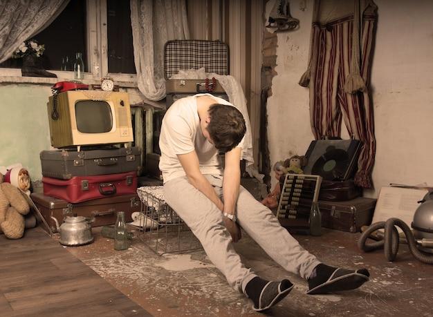 지저분한 버려진 방에서 새장에 앉아있는 동안 낮잠을 취하는 캐주얼 복장의 젊은 남자. 세피아 스타일로 캡처.