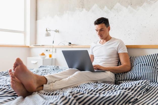 ノートパソコン、自宅で忙しいフリーランサーに取り組んでいる朝のベッドに座っているカジュアルなパジャマの服装の若い男