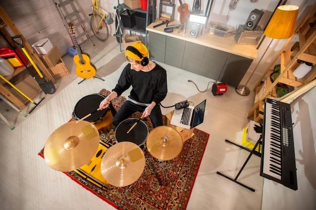 Casualwear 및 드럼을 치는 헤드폰에서 젊은 남자