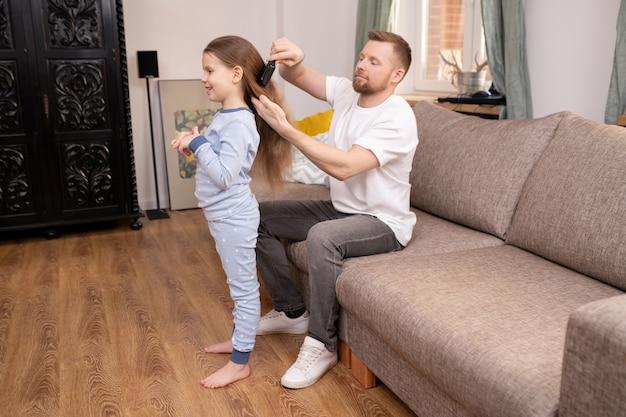 Молодой человек в повседневной одежде сидит на диване и расчесывает длинные волосы своей очаровательной маленькой дочери после утреннего пробуждения