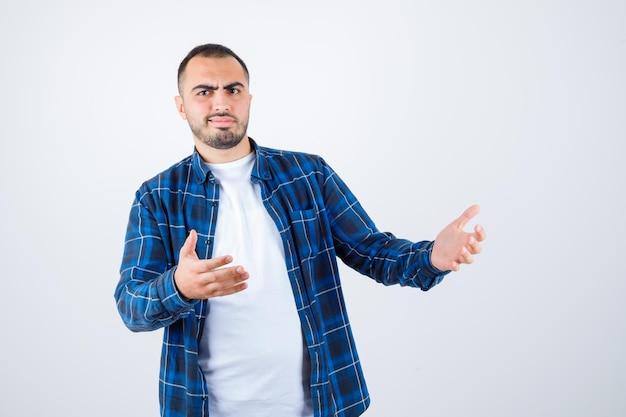 チェックシャツと白いtシャツを着た若い男が何かを受け取ってイライラしているように手を伸ばしています
