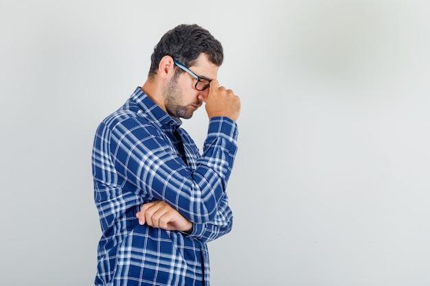 Молодой человек в клетчатой рубашке, в очках смотрит вниз, думает и грустит