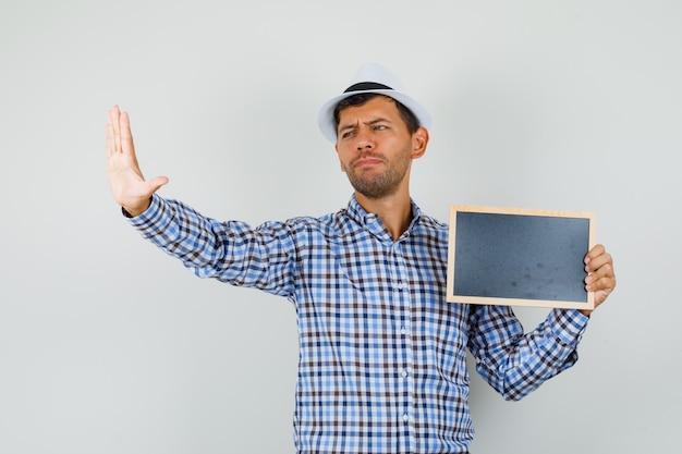 チェックシャツ、空白のフレームを保持している帽子の若い男