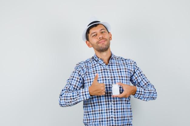 チェックシャツ、丸薬のボトルを保持している帽子の若い男