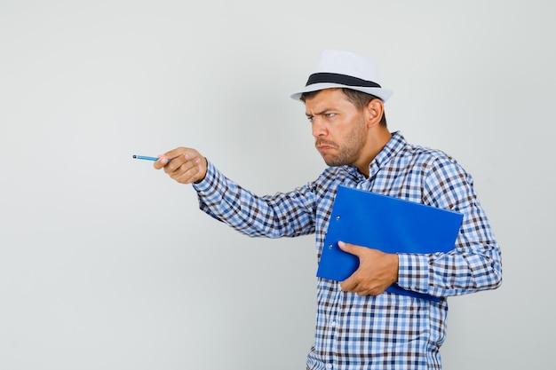 チェックシャツ、クリップボードを保持している帽子の若い男