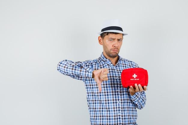 Молодой человек в клетчатой рубашке, шляпе с аптечкой