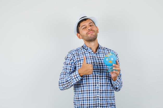 チェックシャツ、帽子保持地球儀の若い男