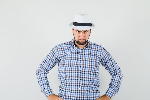 체크 셔츠, 모자 허리에 손을 잡고 심각한, 전면보기를 찾고있는 젊은 남자.