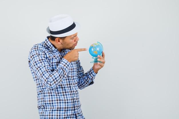 체크 셔츠에 젊은 남자, 세계 세계에서 가리키는 모자와 집중 찾고