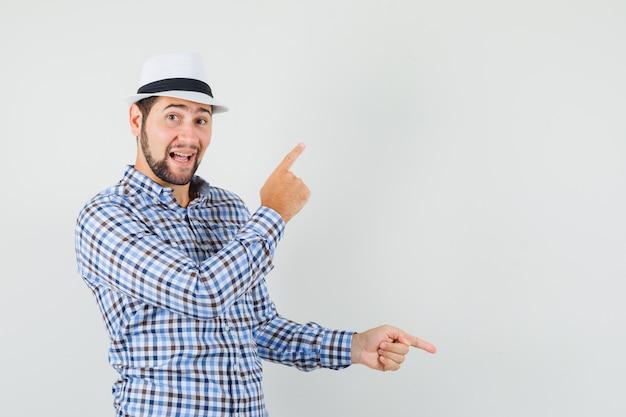 チェックシャツを着た若い男、指を上下に向けて陽気に見える帽子、正面図。