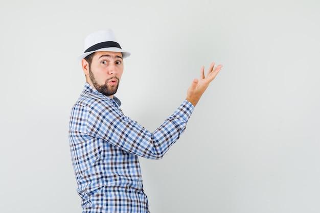 チェックシャツ、帽子を上げて手を上げて、驚いて見える若い男。