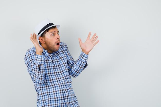 Молодой человек в клетчатой рубашке, шляпа поднимает руки в озадаченном жесте