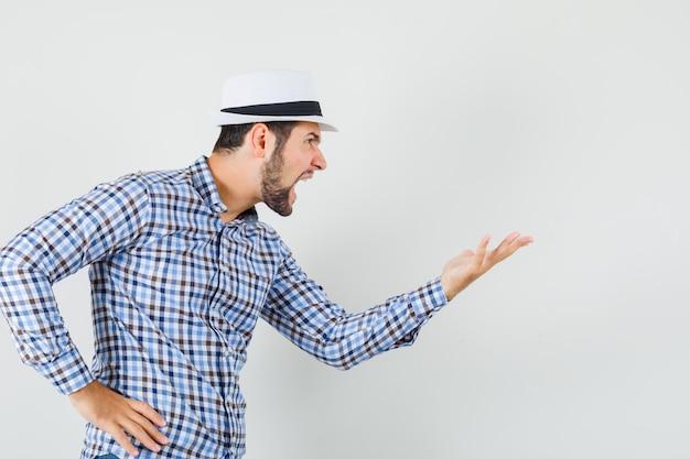 チェックシャツを着た若い男、誰かに向かって叫び、猛烈に見える帽子、正面図。