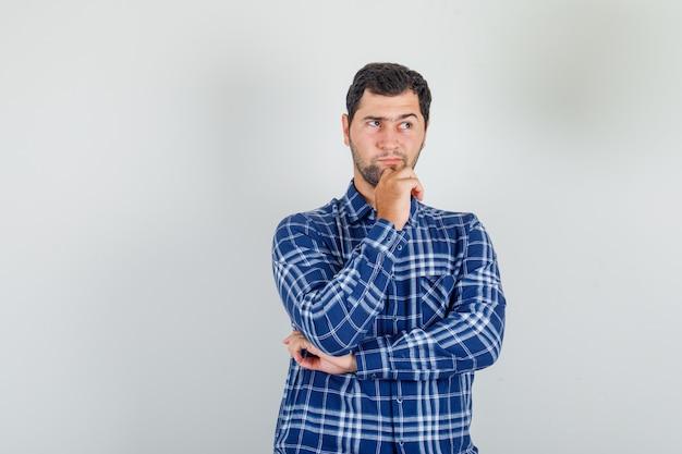 Молодой человек в клетчатой рубашке думает, положив руку на подбородок и выглядит хитро