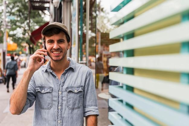 Молодой человек в городе разговаривает по телефону