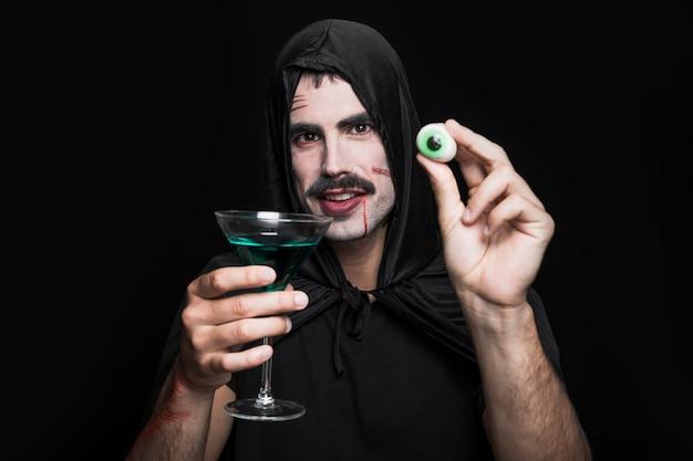 人工的な目と緑の飲み物を持つスタジオでポーズをとる外套の若い男