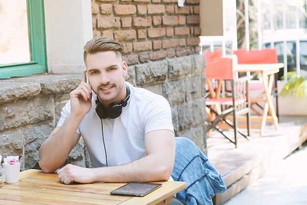コーヒーショップで電話で話す若い男。