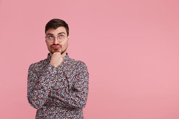 上向きに見ているカラフルなシャツを着た若い男、右側のスペースをコピー、疑問を持って、ピンクの背景で隔離された彼のあごを引っ掻きながら混乱した表情で