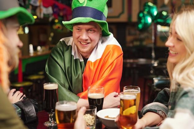パトリックの日を祝う友人とテーブルに座ってビールを飲む衣装を着た若い男