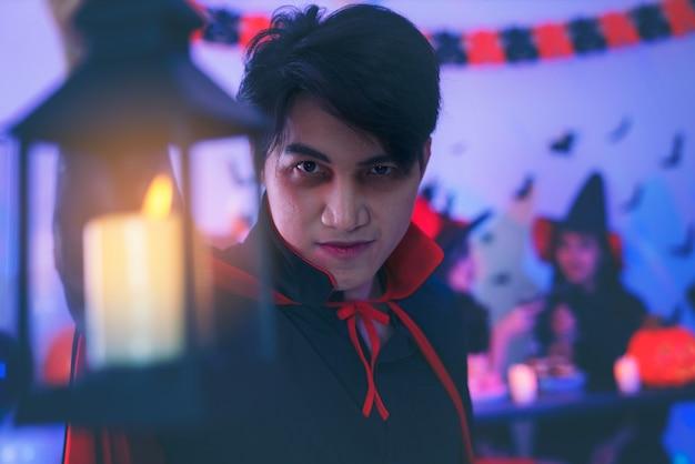Молодой человек в костюмах празднует хэллоуин, развлекаясь на вечеринке в ночном клубе