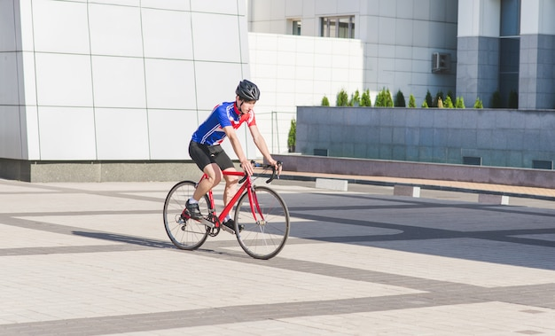 Молодой человек в одежде cycle едет на дорожном велосипеде